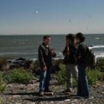 Alejandro Landoni conversa con Eduardo García (Cardona) y Genoveva Malcuori, mientras una turista busca una especie de caracoles que sólo habita en Isla de Flores