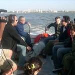 En la embarcación, Adrián Stagi (Ecotours) comienza a relatar la historia de la Isla de Flores a los turistas y al equipo de Producción Nacional – TV Ciudad.