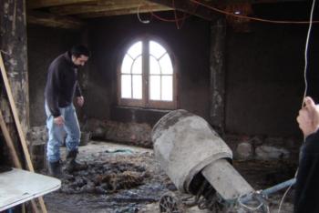 Luciano Davyt, integrante de La Tierrita prepara el barro para revestir las paredes.