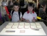 Dos niños juegan con la mesa multitouch.